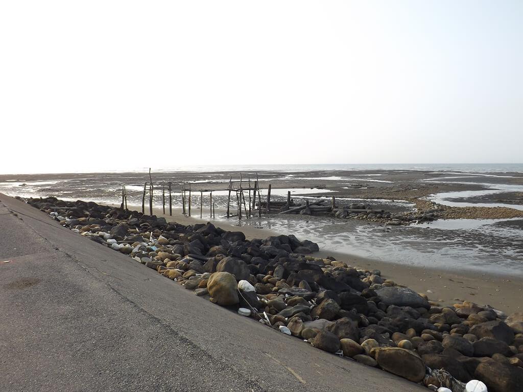 許厝港濕地的圖片:堤防旁的石塊群以及沙灘