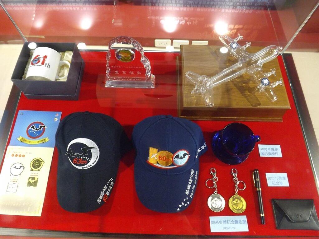 黑蝙蝠中隊文物陳列館的圖片:紀念鴨舌帽、開幕紀念鑰匙圈、紀念筆、玻璃偵察機模型