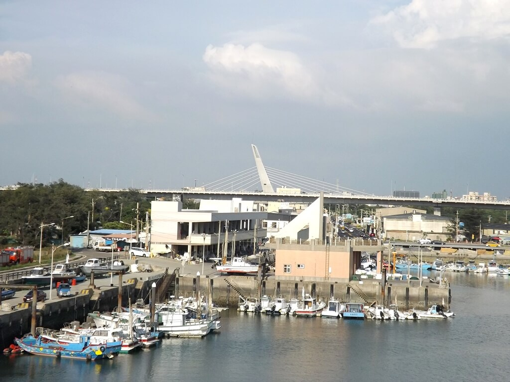 永安漁港的圖片:漁船碼頭及遠方台61號快速道路上的造型