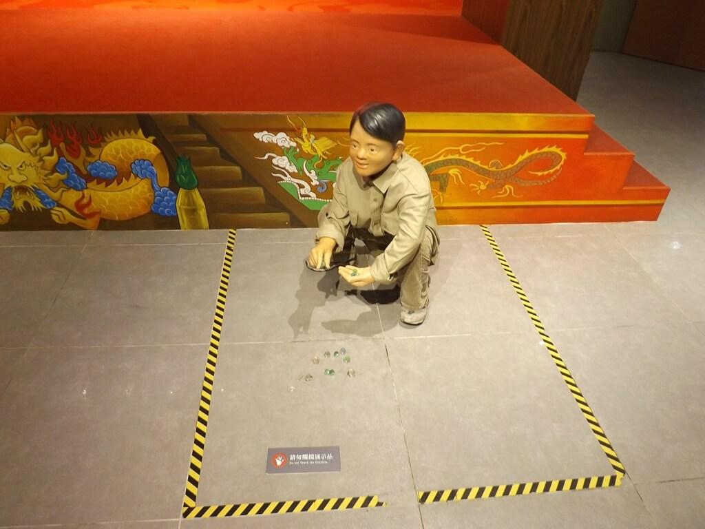 桃園市土地公文化館的圖片:在地上玩著彈珠的學生像