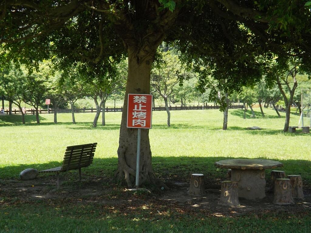 大溪河濱公園的圖片:樹下乘涼區以及禁止烤肉標語