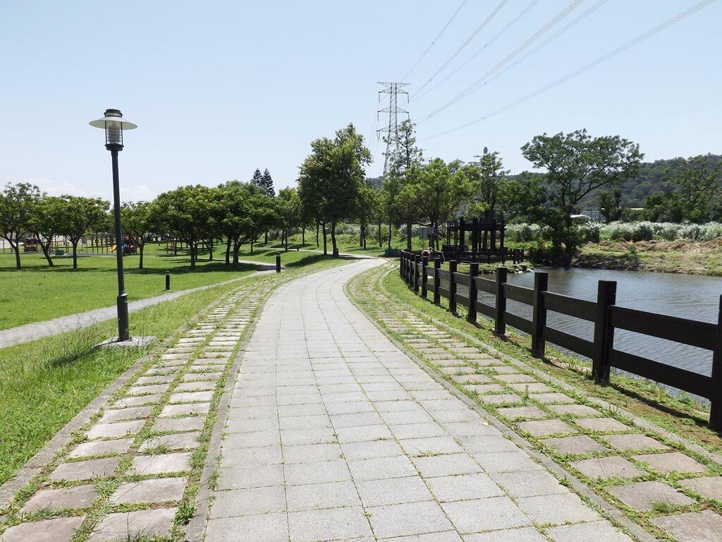 大溪河濱公園的圖片:路燈、公園步道、湖及遠方的高壓電塔