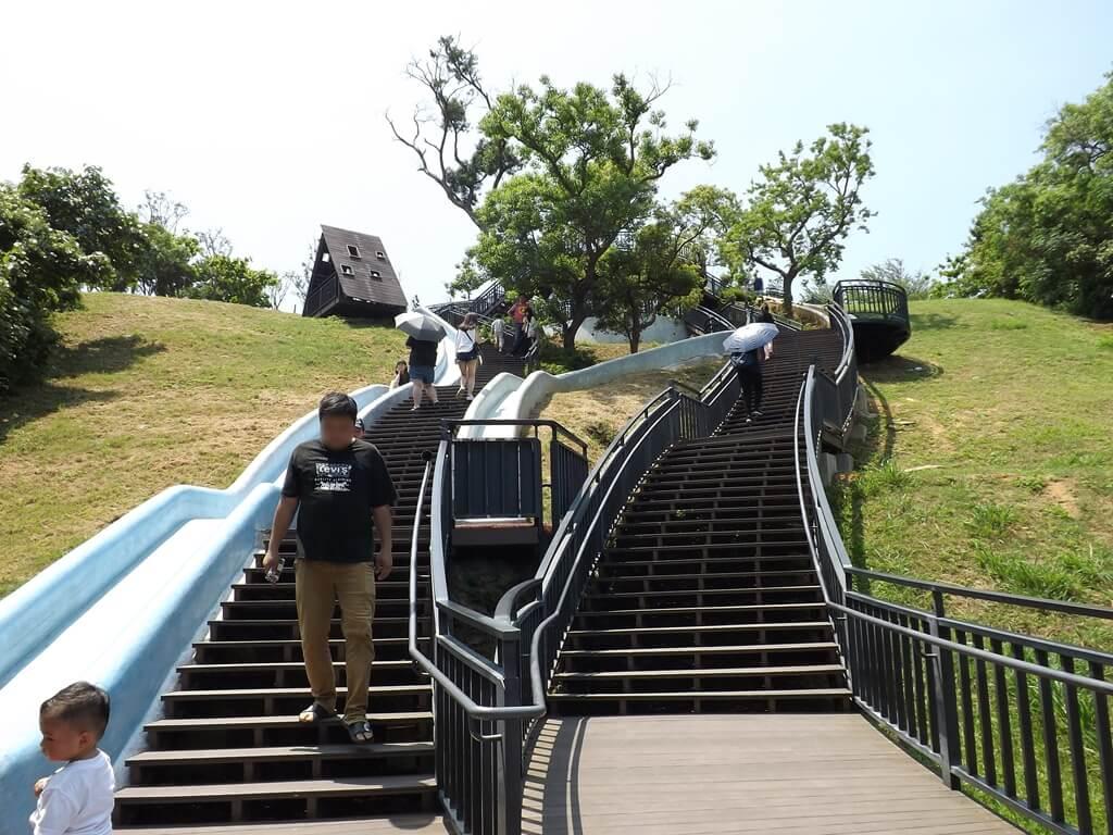 新竹青青草原的圖片:兩條溜滑梯及都是人的兩條木棧步道