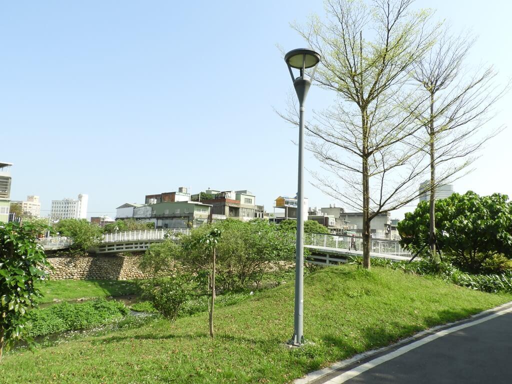 中壢老街溪步道的圖片:老街溪河濱步道旁的翠堤橋及綠地美景